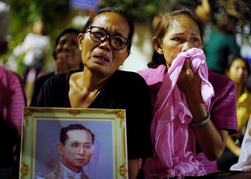 10月13日、タイ王室はプミポン国王が同日に病院で死去したと発表した。写真は、国王死去のニュースを聞き涙を流す人々。13日、バンコクで撮影(2016年 ロイター/Jorge Silva)